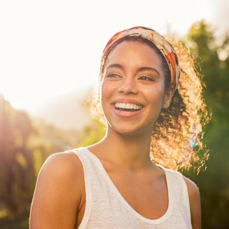 Lachende Frau mit strahlend weißen Zähnen in sonnenbeschienener Natur