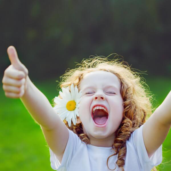 lockiges Kleinkind in der Natur mit Blume im Haar freut sich mit gesunden weißen Zähnen und Daumen hoch