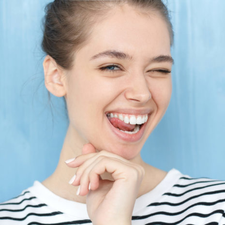 Freche junge Frau zwinkert mit strahlend weißen Zähnen
