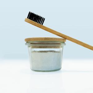 Zahnpulverglas mit angelehnter Bambuszahnbürste