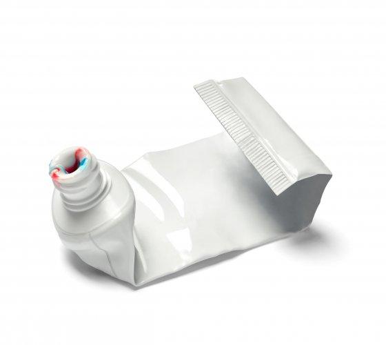 ausgequetschte Zahnpasta-Plastiktube mit weiß-rot-blauem Zahnpastarest an der Öffnung